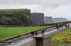 DUBLIN, IRELAND - FEBRUARY 17, 2017: The Cliffs of Moher attractions. People going to see the beautiful cliffs stock images