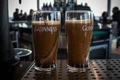 DUBLIN, IRELAND - FEBRUARY 7, 2017: Two pints of Guinness on a stand almost ready to drink inside the Guinness Storehouse stock photography