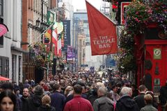 Temple Bar Neighborhood of Dublin, Ireland During a Busy Afternoon. Dublin, Ireland - June 7, 2019: A large crowd of people is shown down the main street of the stock photo