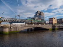 Dublin, Ireland - River Liffey Bridge, and Rail Bridge with DART train royalty free stock image
