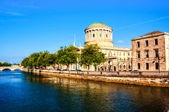 Sunlighted Four courts building in Dublin, Ireland with river Liffey royalty free stock image