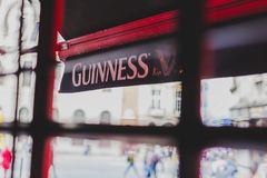 Guinness logo on pub`s awnings shot from inside the window. DUBLIN, IRELAND - 28th March, 2018: Guinness logo on pub`s awnings shot from inside the window Royalty Free Stock Photo