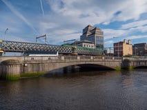 Dublin, Irland - Fluss Liffey-Kolben-Brücke und Bahnbrücke mit PFEIL-Zug lizenzfreies stockbild