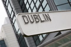 Dublin Signpost avec le bâtiment photos stock