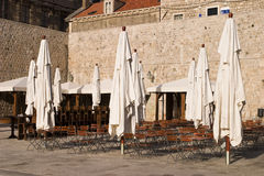 Dubrovnik Cafe. A cafe in Dubrovnik, Croatia is waiting with empty tables and furled umbrellas for the first customers. It is located next to the harbor and old royalty free stock images
