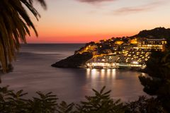 The Dubrovnik coast illuminated with orange light at night. royalty free stock photography