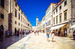 Tourists walk along paved stone streets of old city of Dubrovnik on warm sunny day, Dubrovnik, Croatia. royalty free stock images