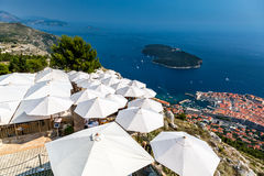 Dubrovnik Croatia. Top view over restaurant with sun umbrellas and the old town below. Royalty Free Stock Photography