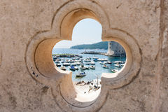 Dubrovnik harbor through feature opening. In ancient wall Royalty Free Stock Photo