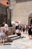 Dubrovnik Kroatien, Juni 2015 Gatamusiker i nationella kläder och turister i fyrkanten av den gamla staden royaltyfri foto