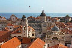 Dubrovnik Old City Cathedral View with The Sea. City view of the cathedral and the sea over the rooftops of the old buildings. Colorful parachute is passing Stock Photo
