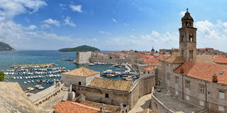 Dubrovnik Old Town. Panorama of Old City of Dubrovnik shows port with boats and yachts, city walls, fortification, rooftops and Dominican church tower Royalty Free Stock Image