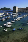 Dubrovnik port and tower. Dubrovnik port with boats and castle stock images