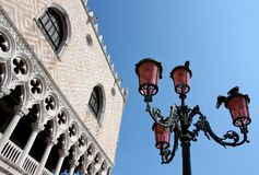 The Ducal Palace in Venice, Italy. The Ducal Palace of Venice and a typical lamp with pigeons Stock Photography
