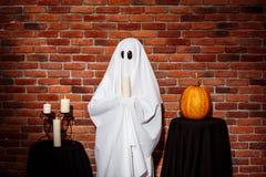 Duch trzyma świeczkę nad ceglanym tłem Halloween przyjęcie Fotografia Royalty Free
