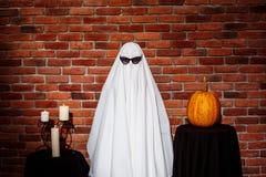 Duch w okularach przeciwsłonecznych pozuje nad ceglanym tłem Halloween przyjęcie Zdjęcia Stock