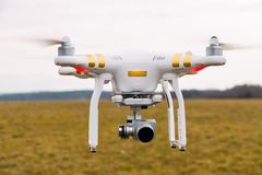 Duchonka, Slovakia- 03. 11. 2018. White flying drone quad copter with high resolution digital camera with gimbal with meadow on ba. White flying drone quad Royalty Free Stock Photos