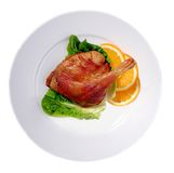 Duck. Leg prepared on a plate decorated with leaves of salad and an orange Stock Photos