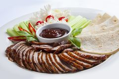 Duck in Beijing with cucumbers and pancakes. Sliced in pieces royalty free stock photos