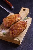 Duck breast, lavender honey and rosemary, served on chopping board. Duck breast, lavender honey and rosemary, served on chopping board royalty free stock photography