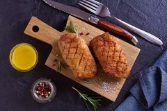 Duck breast, lavender honey and rosemary, served on chopping board. View from above, top studio shot stock photography