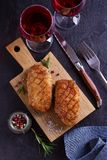 Duck breast, lavender honey and rosemary, served on chopping board. Duck breast, lavender honey and rosemary, served on chopping board, glasses of red wine stock photo