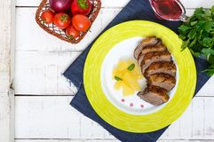 Duck breast Magret with pieces of pineapple on a ceramic plate on a white wooden background. French traditional meat dish. Christmas menu. Festive kitchen. The royalty free stock photos