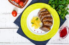 Duck breast Magret with pieces of pineapple on a ceramic plate on a white wooden background. French traditional meat dish. Christmas menu. Festive kitchen. The stock images
