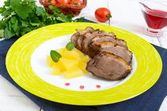 Duck breast Magret with pieces of pineapple on a ceramic plate on a white wooden background. French traditional meat dish. Christmas menu. Festive kitchen stock photography