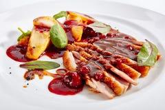 Duck Breast mit Bratapfel-und Pfirsich-Creme auf elegantem Restaura lizenzfreie stockfotografie
