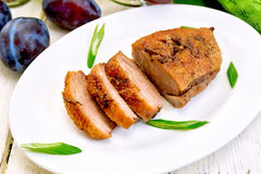 Duck breast with plum sauce and green onions in white plate. Roasted duck breast with green onions in a white oval plate, towel and plums on a background of Stock Image