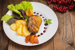 Duck breast with potato chips, herbs, sauce and caramelized apples. Wooden rustic table. Top view. Close-up Royalty Free Stock Image