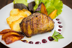 Duck breast with potato chips, herbs, sauce and caramelized apples. Wooden rustic table. Top view. Close-up Stock Photography