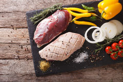 Duck breast raw, with vegetables and spices close-up on a board. Duck breast raw, with fresh vegetables and spices close-up on a cutting board. horizontal view Royalty Free Stock Images