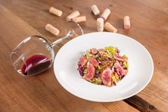 Duck breast salad with glass of red wine stock image