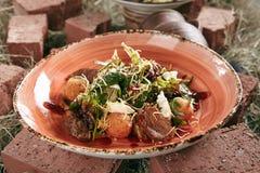 Duck Breast Salad med frasiga potatisbollar på lantligt stilhö B fotografering för bildbyråer