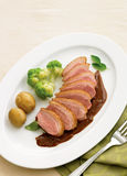 Duck breast with wine and chocolate sauce. Sliced duck breast on wine and chocolate sauce with baby potatoes, green cauliflower and basil leave with fork on a Royalty Free Stock Photo