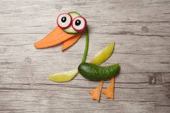 Duck compiled of raw vegetables on wooden board. Duck made of carrot, cucumber, pepper, onion, radish and olive. Shot with Canon 760D, ISO 100. Wooden background Royalty Free Stock Photography