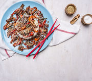 Duck con el arroz y el sésamo, receta asiática, palillos rojos, condimentos, en una frontera azul de la placa, parte posterior rú Fotografía de archivo