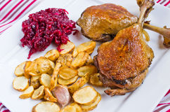 Duck confit with beetroots and jerusalem artichokes fries. Traditional duck legs confit with beetroots and jerusalem artichokes fries Royalty Free Stock Photos