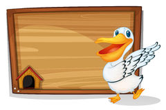 A duck dancing beside a wooden blank board Stock Photo