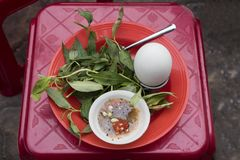 Duck embryo eggs, sauce and herbs on a stool at a street restaurant in Vietnam. Duck embryo eggs, sauce and herbs on a stool at a street restaurant in Ho Chi royalty free stock photo