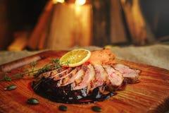 Duck a faixa em uma superfície de madeira com molho preto e alaranjado, alecrins e cenouras, um ajuste acolhedor da tabela, again fotografia de stock