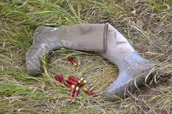 Duck hunter drops boots and shells on ground. A duck or goose hunter drops his knee high water boots and shotgun shells on the grass of a slough Royalty Free Stock Images