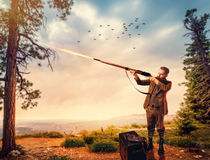 Duck hunter in hunting clothing aims an old rifle. Duck hunter man in vintage hunting clothing aims an old rifle in forest. Hunt lifestyle, antique weapon Stock Image