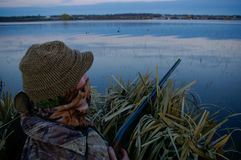 Duck Hunter In Blind With Shotgun. Duck hunter sits in a blind during the early morning with his shotgun Stock Image