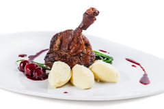 Duck leg baked with cherry and mashed potatoes.  royalty free stock photo