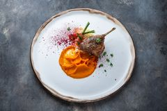 Duck leg confit with batat puree, carrots and couscous, restaurant meal royalty free stock photography
