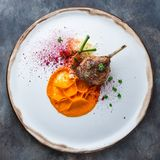 Duck leg confit with batat puree, carrots and couscous, restaurant meal royalty free stock photos