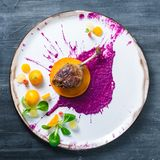 Duck leg confit with cabbage puree and persimon on white plate, restsurant meal royalty free stock photos